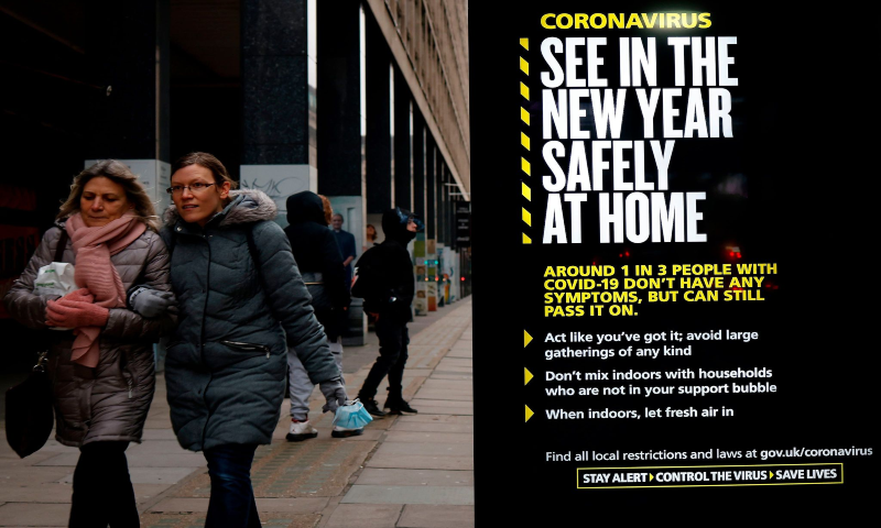 Pedestrians walk past a bus stop with a government message about the coronavirus tier four restrictions urging people to stay home in London on Dec 29, 2020. — AFP