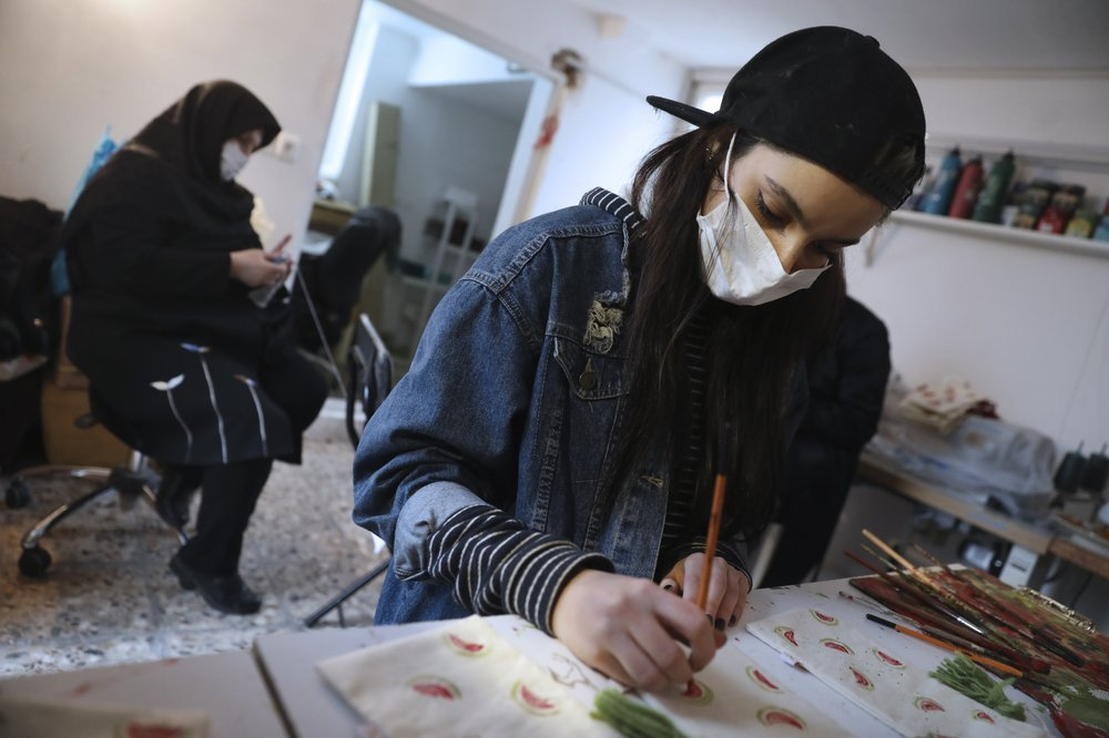 Bahareh Eskandarkhan paints on a cloth bag at a workshop of Bavar charity in Tehran. ─ AP