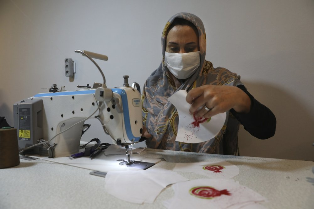 Elham Karami sews a protective face mask at a workshop of Bavar charity in Tehran. ─ AP