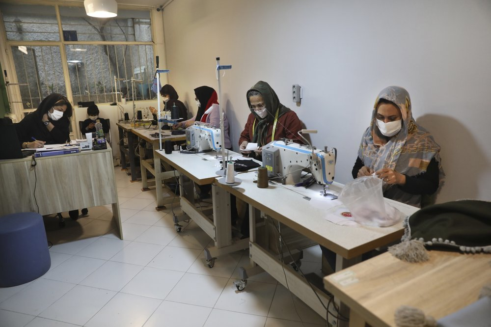 Women sew protective face masks at a workshop of Bavar charity in Tehran. ─ AP