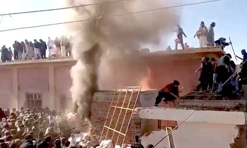 The shrine seen on fire as a large crowd is present in Karak district of KP. — Screengrab