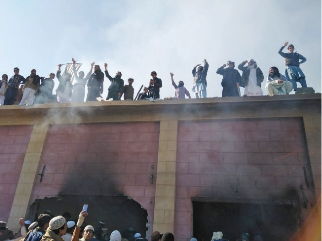 Villagers stand on the roof of the shrine after setting it on fire in Karak. (Below) A damaged portion of the Hindu Samadhi. — Dawn