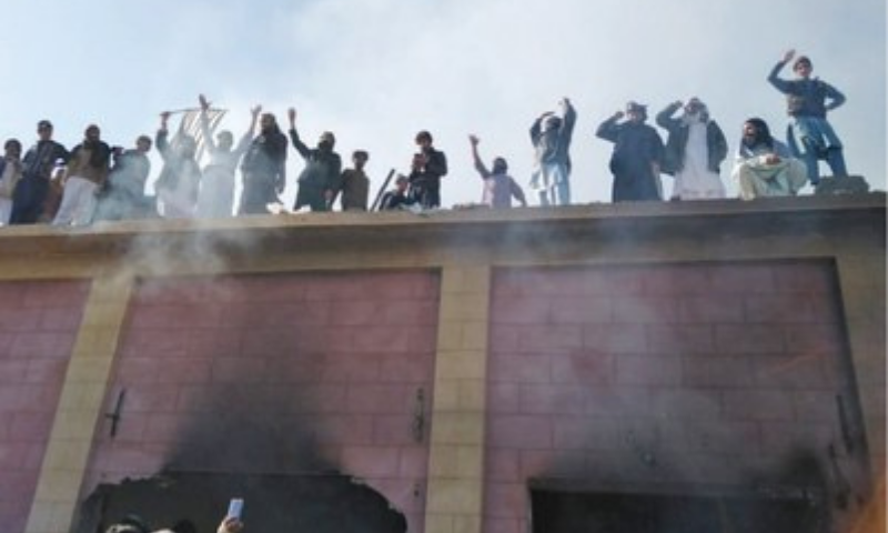 Villagers stand on the roof of the shrine after setting it on fire in Karak. — Dawn