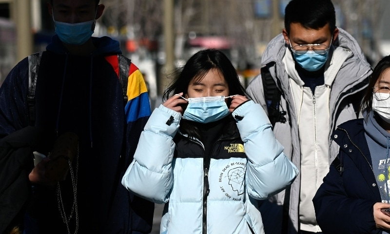 People wearing face masks walk along a street in Beijing on December 31. — AFP