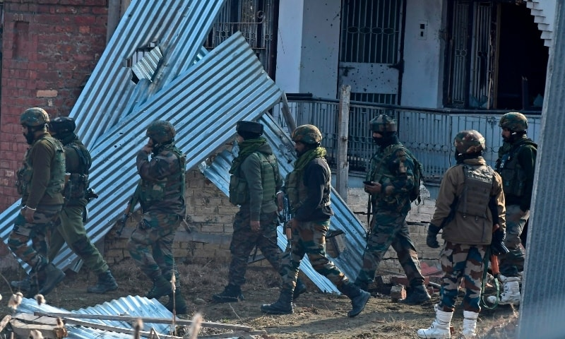 Indian army soldiers walk past a damaged house after a gunbattle between suspected Kashmiri fighters and government security forces at Lawaypora area on the outskirts of Srinagar on December 30, 2020. — AFP
