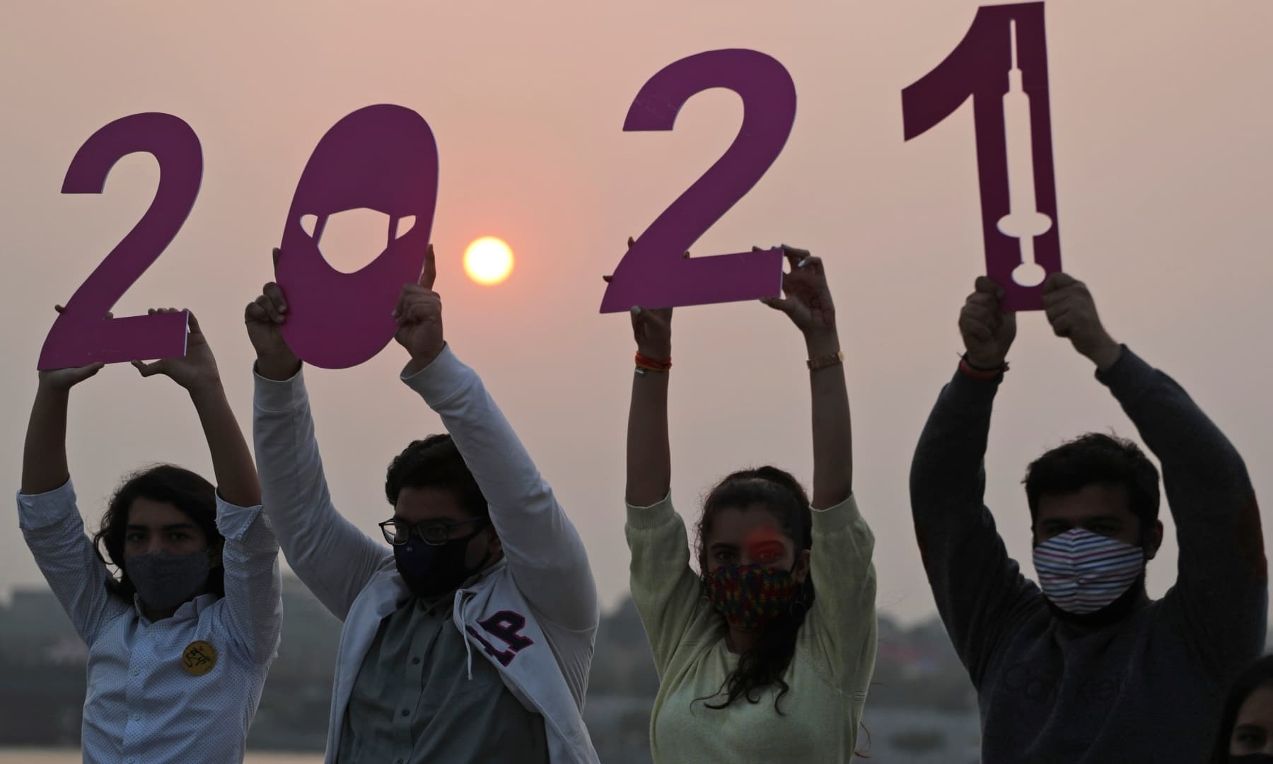Indians hold cutouts welcoming 2021 on New Year's Eve in Ahmedabad, India, Thursday. — AP
