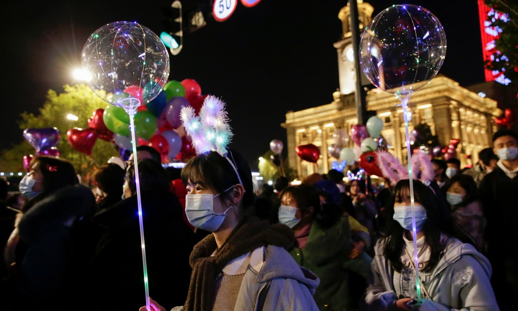 Women hold light balloons as people gather to celebrate the arrival of the new year during the coronavirus outbreak in Wuhan, China, Dec 31. — Reuters