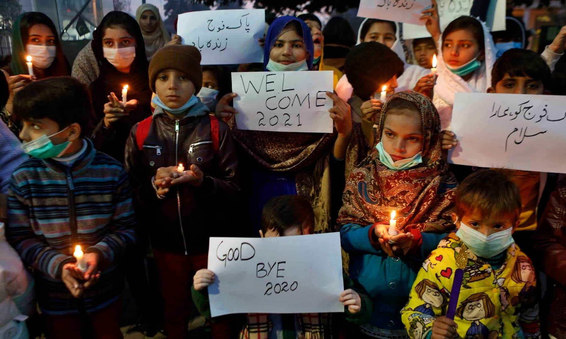 Children hold candles and take part in a demonstration to welcome the new year, in Lahore, Thursday. — AP