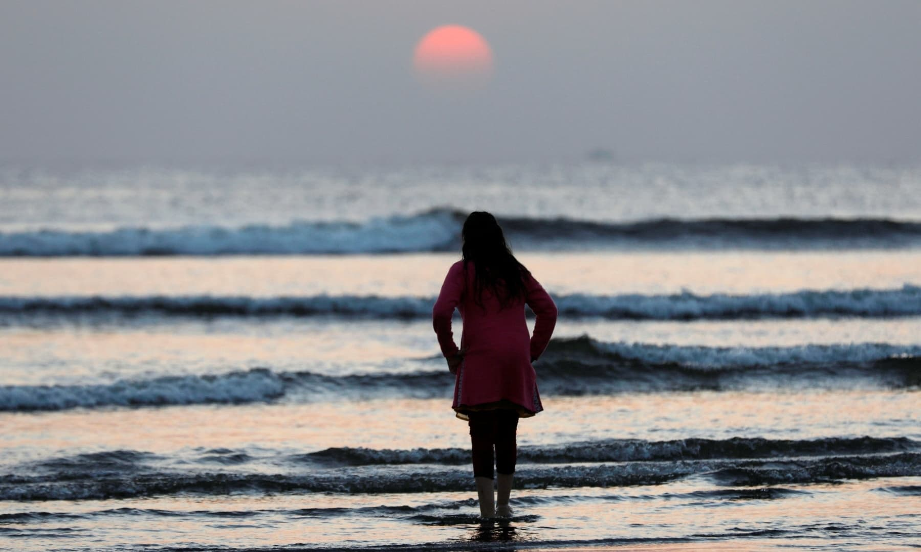 A girl stands amid sea waters as the sun sets on New Year's Eve at Clifton Beach in Karachi. — Reuters