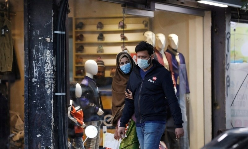 A couple wearing protective masks walk along a market, as the outbreak of coronavirus disease continues, in Karachi, Pakistan December 29. — Reuters/File