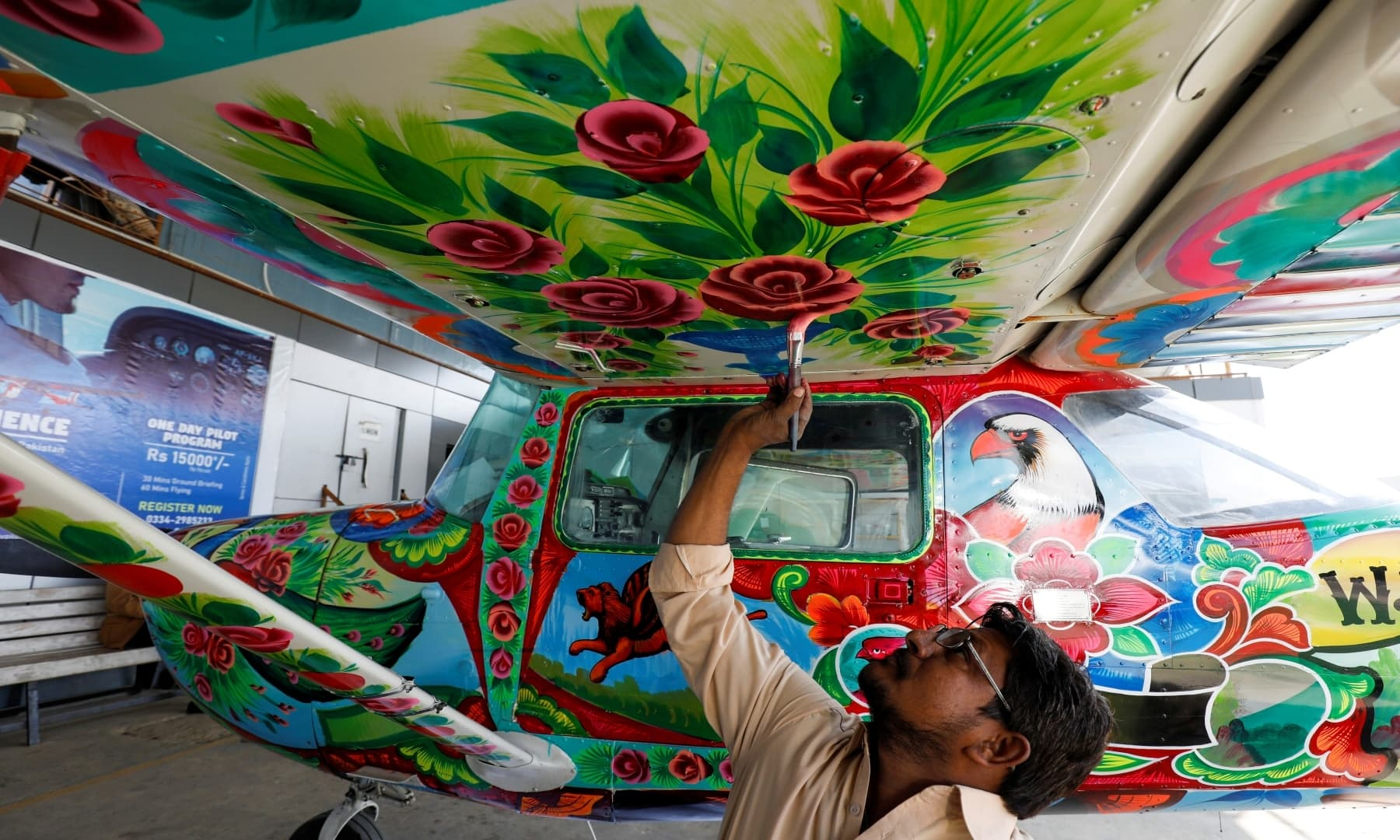A man paints a two-seater Cessna aircraft with Pakistani truck art at Jinnah International Airport, Dec 30, 2020. — Reuters
