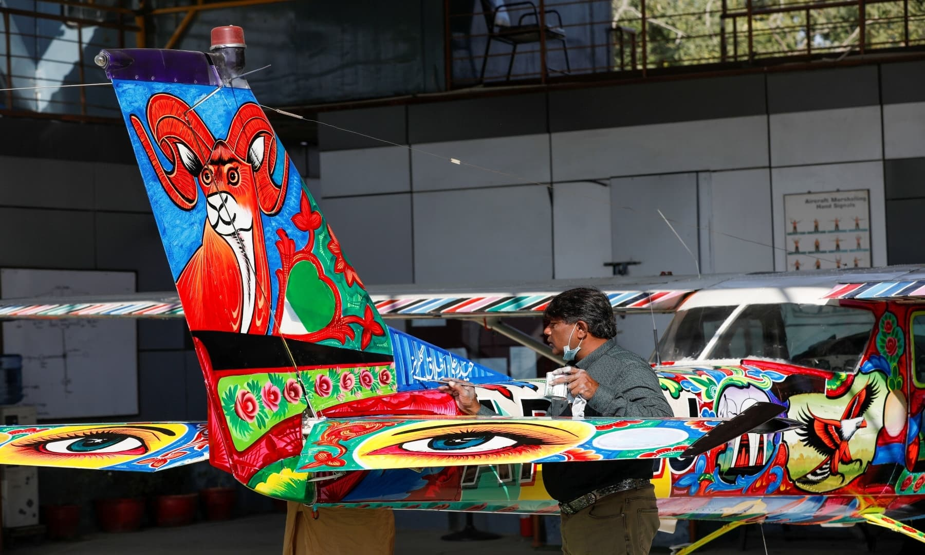 Haider Ali decorates a two-seater Cessna aircraft with Pakistani truck art at Jinnah International Airport, Karachi, Dec 30, 2020. — Reuters