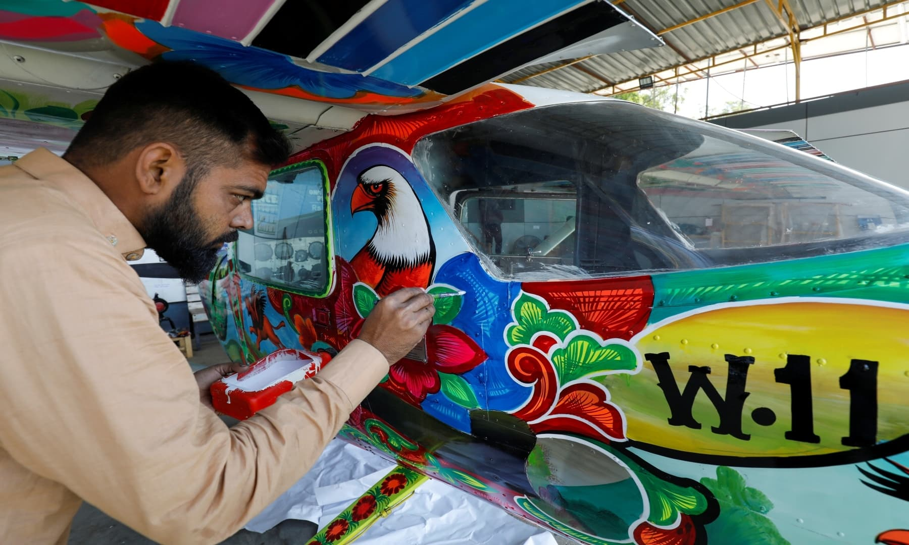A man paints Pakistani truck art on a two-seater Cessna aircraft at general aviation area at Jinnah International Airport, Dec 30, 2020. — Reuters