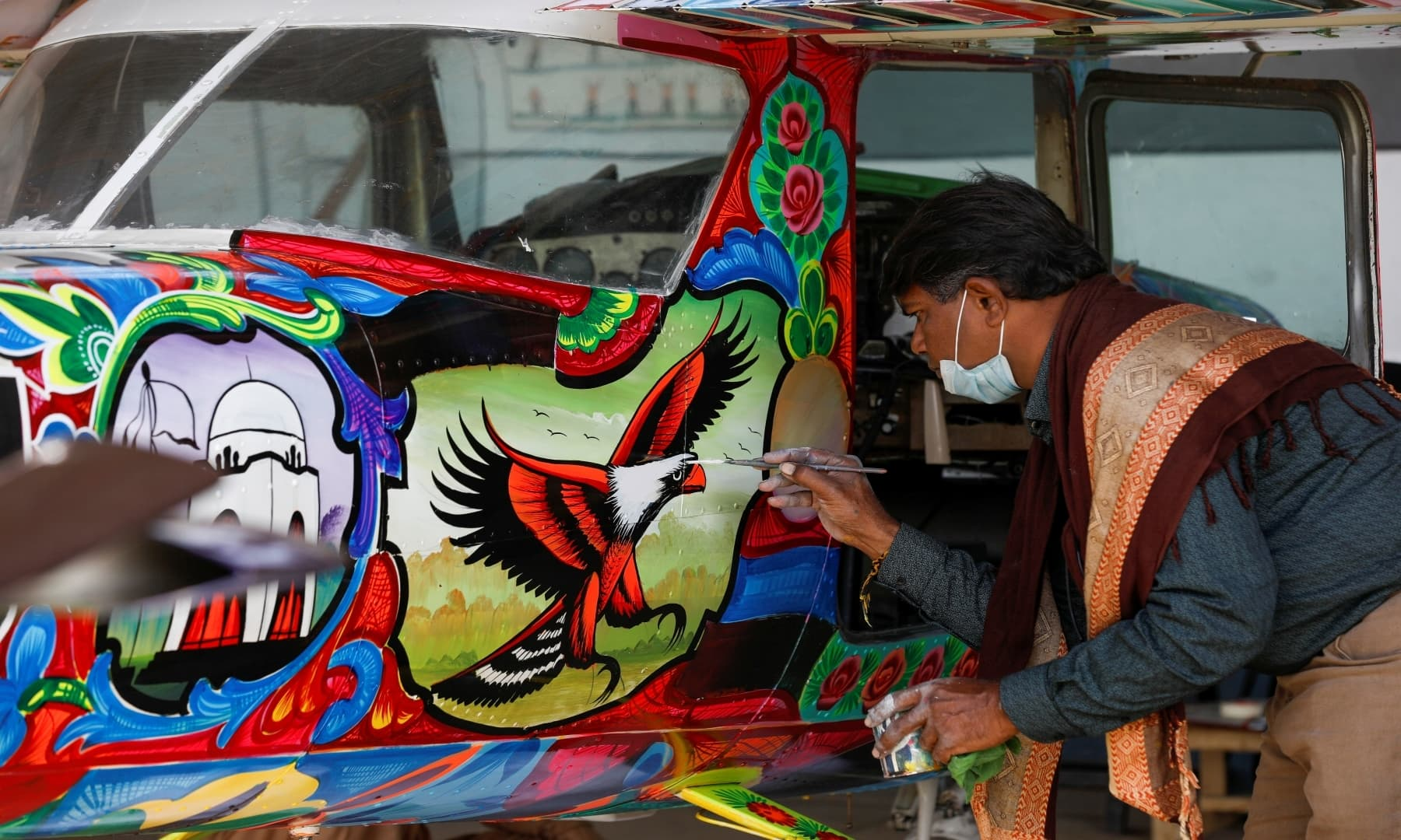 Painter Haider Ali paints Pakistani truck art on a two-seater Cessna aircraft at the Jinnah International Airport, Karachi, Dec 30, 2020. — Reuters