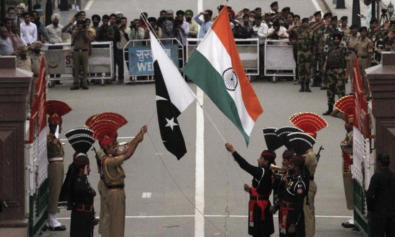 Pakistan Rangers (wearing black uniforms) and Indian Border Security Force (BSF) officers lower their national flags during a daily parade at the Pakistan-India joint check-post at Wagah border in this file photo. — Reuters