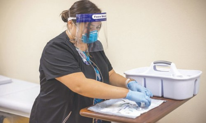 This Dec 29, 2020, photo provided by Johns Hopkins Centre for American Indian Health, a registered nurse prepares a coronavirus vaccine in Chinle, Arizona, for someone who received a placebo.—AP