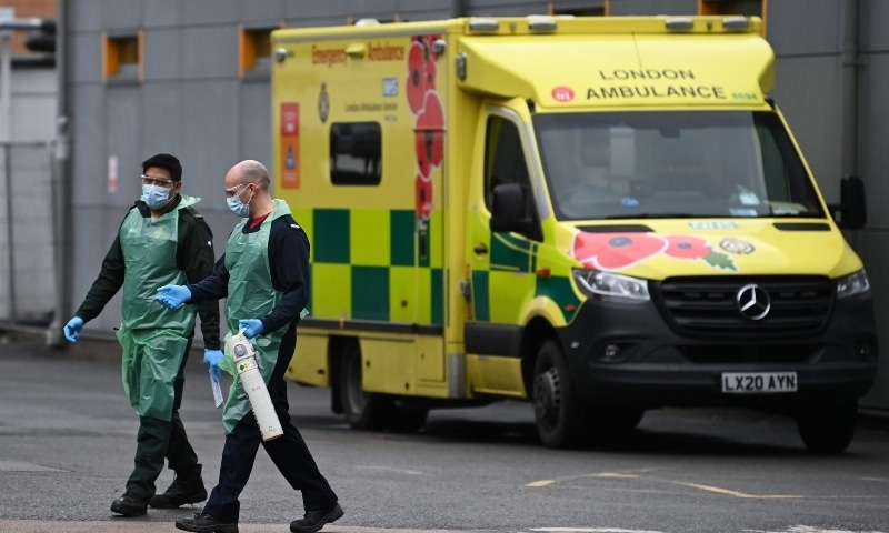 Medics carry an oxygen cannister in the ambulance park outside Lewisham Hospital in south London on January 3. - AFP