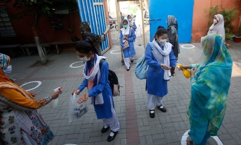 Teachers disinfect hands of students upon their arrival at a school in Lahore on September 15, 2020. — AP/File