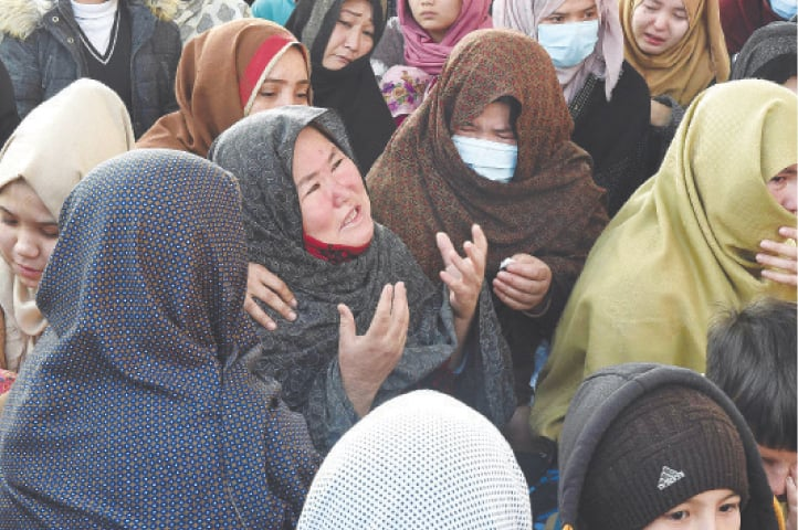 MOURNERS from the Shia Hazara community react as they hold a sit-in near Quetta on Monday along with the coffins of the coal miners who were killed in the Mach area on Sunday.—AFP