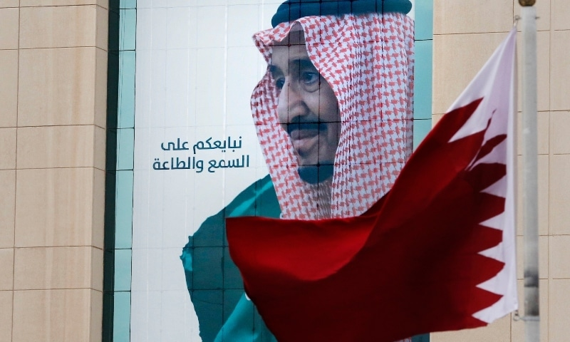 """In this 2019 file photo, a Qatari flag flies in front of a banner showing Saudi King Salman with Arabic writing that reads, """"We pledge you to listen and obey"""" at a trade center in Riyadh. —  AP"""