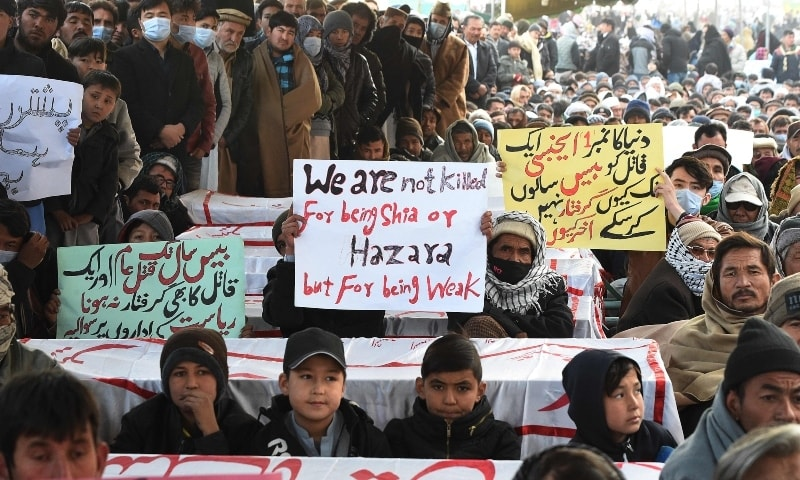 Mourners from the Shia Hazara community gather near coffins of the slain miners during a sit-in protest at the eastern bypass on the outskirts of Quetta on January 5. — AFP