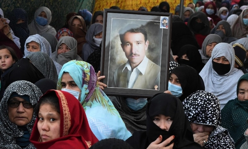 A mourner from the Shia Hazara community holds the portrait of a victim during a sit-in on the outskirts of Quetta. — AFP