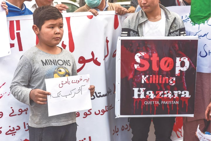 Young boys hold up placards outside the KPC. —Fahim Siddiqi/Shakil Adil/White Star
