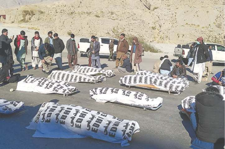 Members of the Shia Hazara community stand around the bodies of 11 coal miners in the Mach area of Balochistan on Sunday. — AFP/File