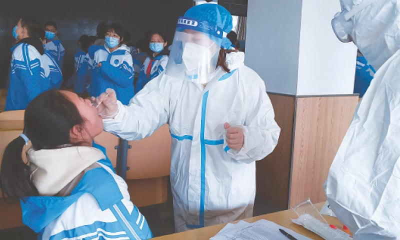XINGTAI (China): A medical worker in a protective suit collects a swab sample from a school student during mass testing following a new Covid-19 outbreak here on Wednesday.—Reuters