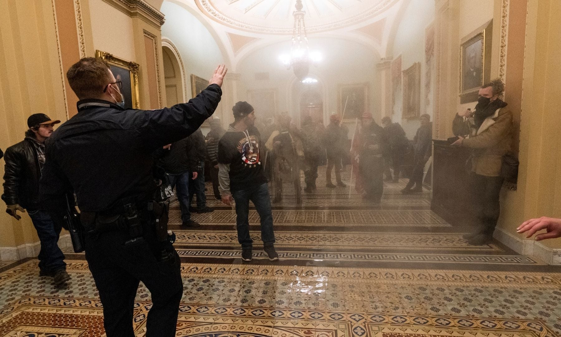 Smoke fills the walkway outside the Senate Chamber as supporters of President Donald Trump are confronted by US Capitol Police officers inside the Capitol. — AP