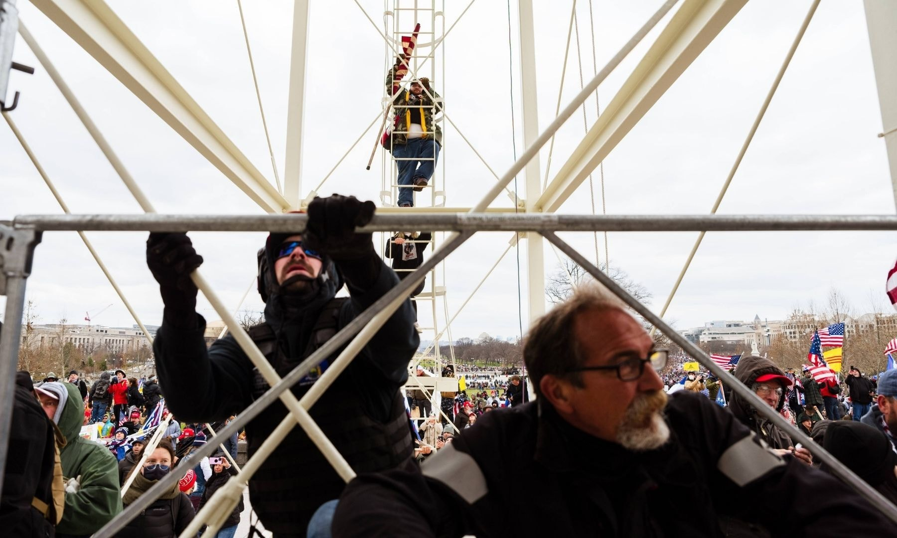 Protesters climb the scaffolding on the inauguration platform after breaking through barriers onto the grounds of the Capitol Building. — AFP