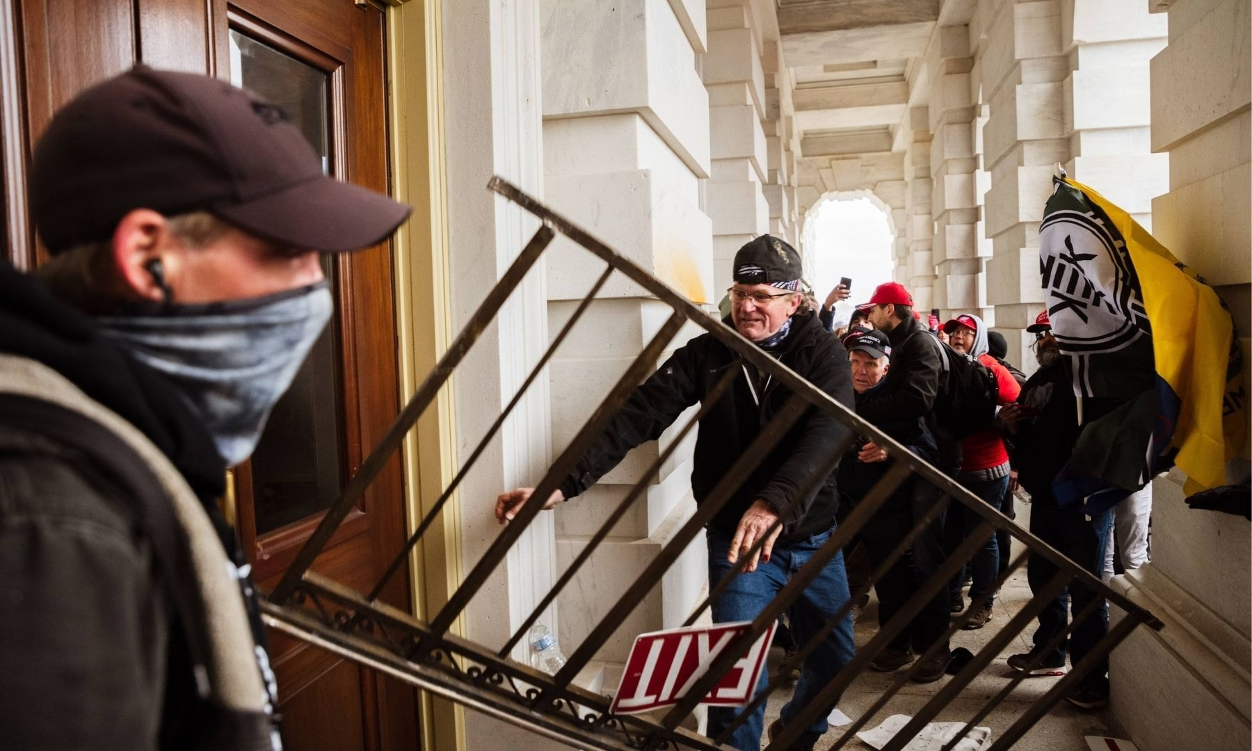 A member of a pro-Trump mob bashes an entrance of the Capitol Building in an attempt to gain access. — AFP