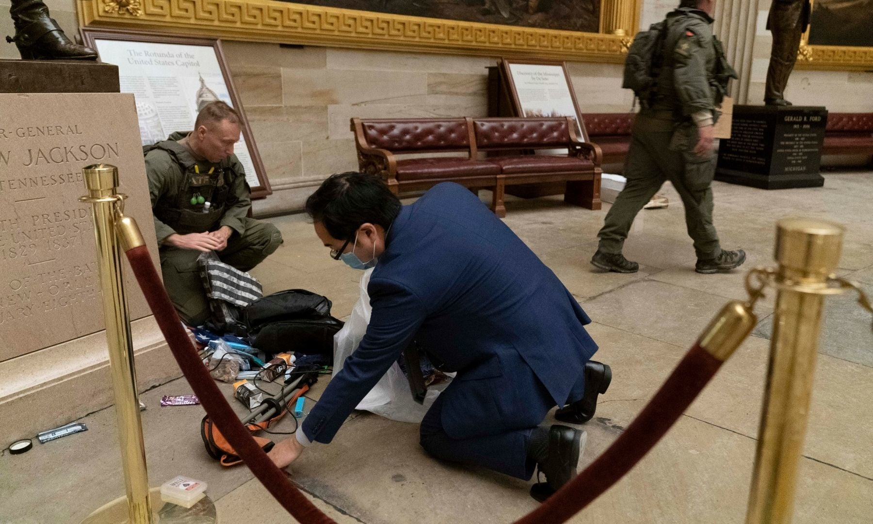 Rep. Andy Kim, D-N.J., helps ATF police officers clean up debris and personal belongings strewn across the floor of the Rotunda in the early morning hours of Thursday. — AP