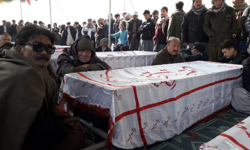Members of the Shia Hazara community stage a protest along with coffins containing the miners' bodies in the western bypass area in Quetta on Thursday. — Photo by Ghalib Nihad