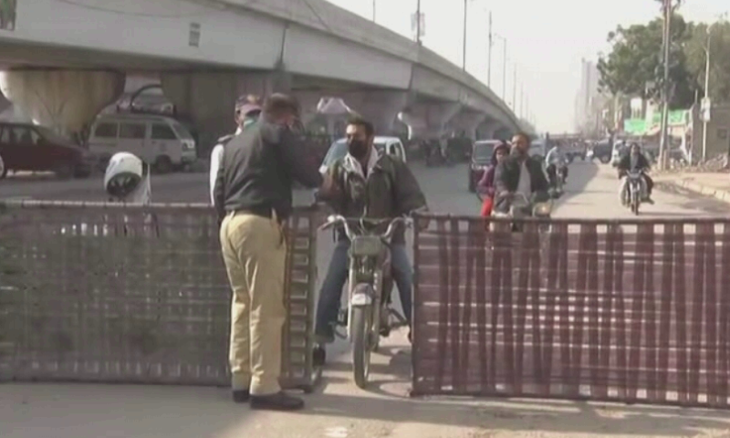 A police officer questions a motorcyclist looking to pass through a blocked road in Karachi on Thursday. — DawnNewsTV