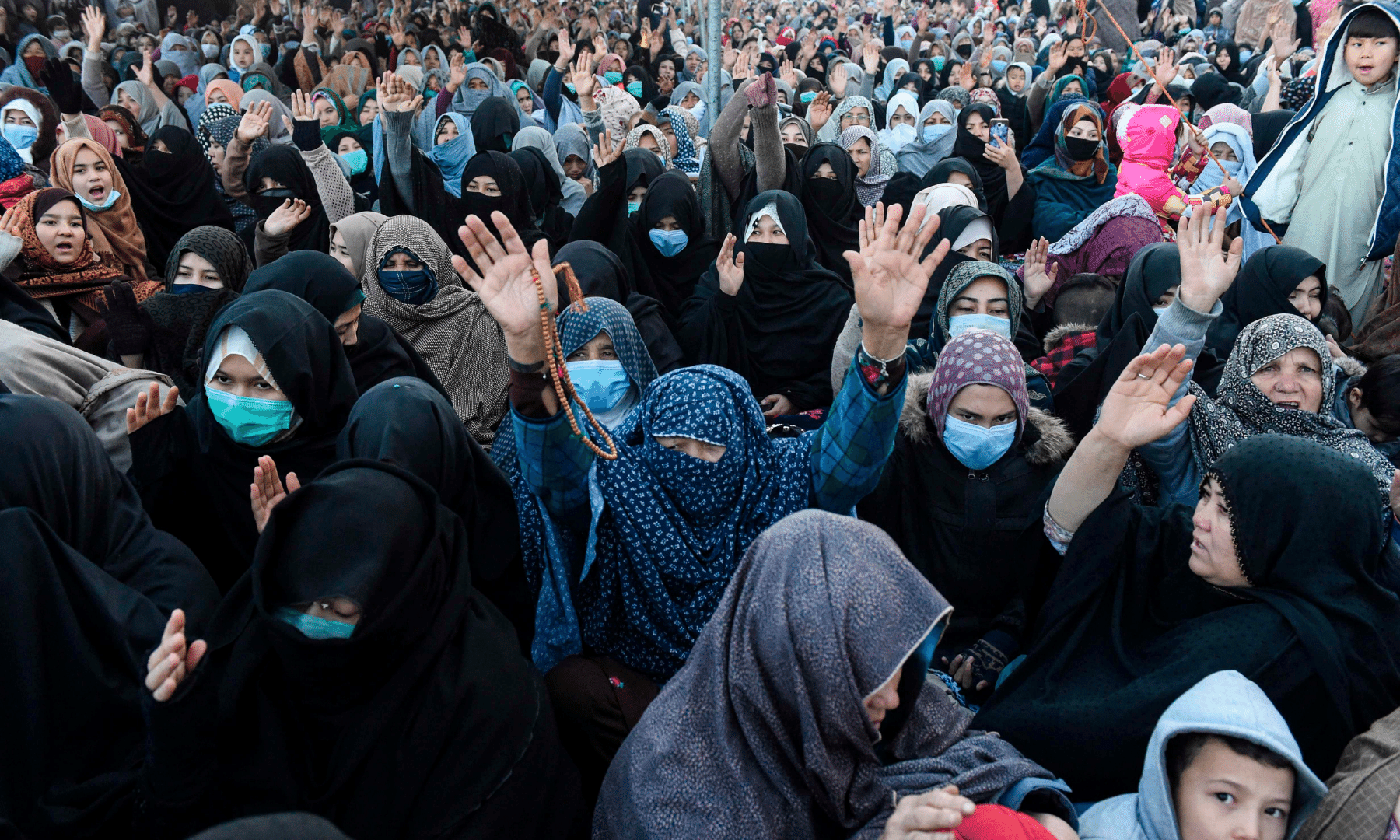 Mourners from the Shia Hazara community gather near the coffins of miners who were killed in an attack by gunmen in the mountainous Machh area, during a sit-in protest on the outskirts of Quetta on Wednesday. — AFP