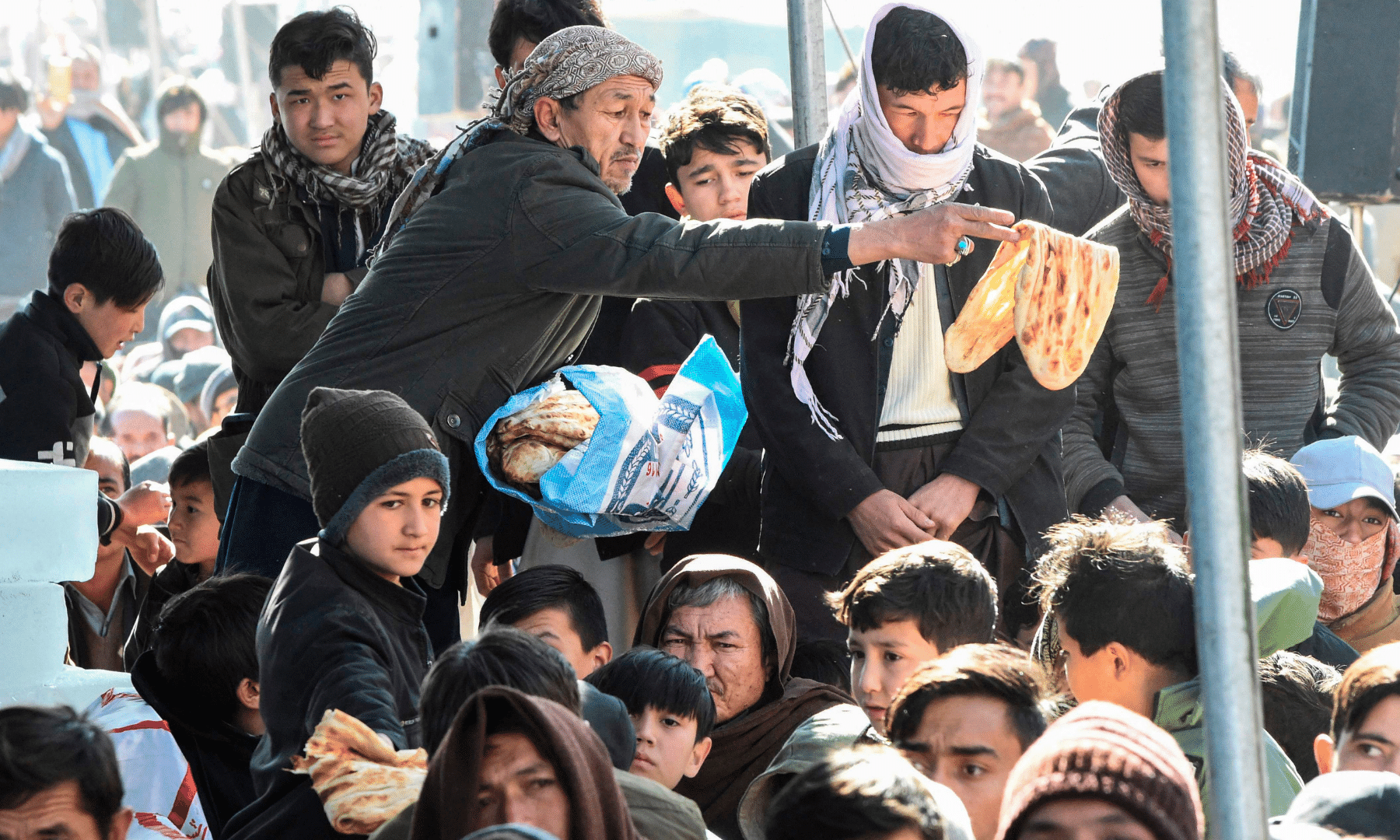 A man distributes bread to mourners during a sit-in protest on the outskirts of Quetta on Jan 6. — AFP