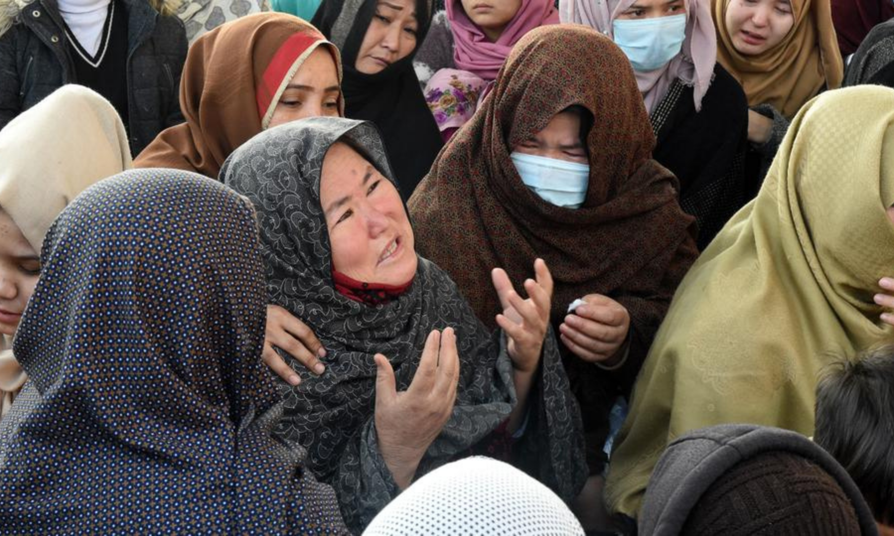 Mourners react as they gather with coffins of miners during a sit-in protest on the outskirts of Quetta on Jan 4. — AFP