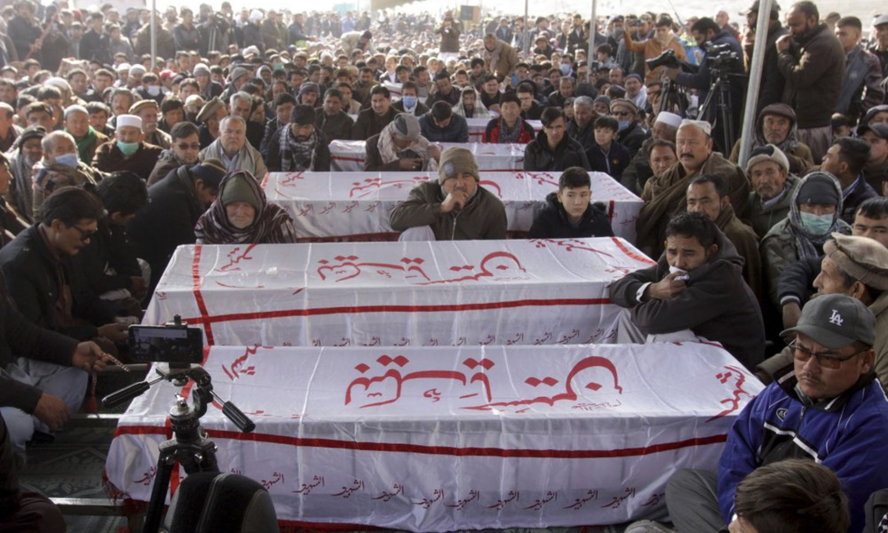 People from the Shia Hazara community gather around the caskets of coal mine workers who were killed by unknown gunmen near the Machh coalfield, during a sit-in protest, in Quetta on Monday. — AP