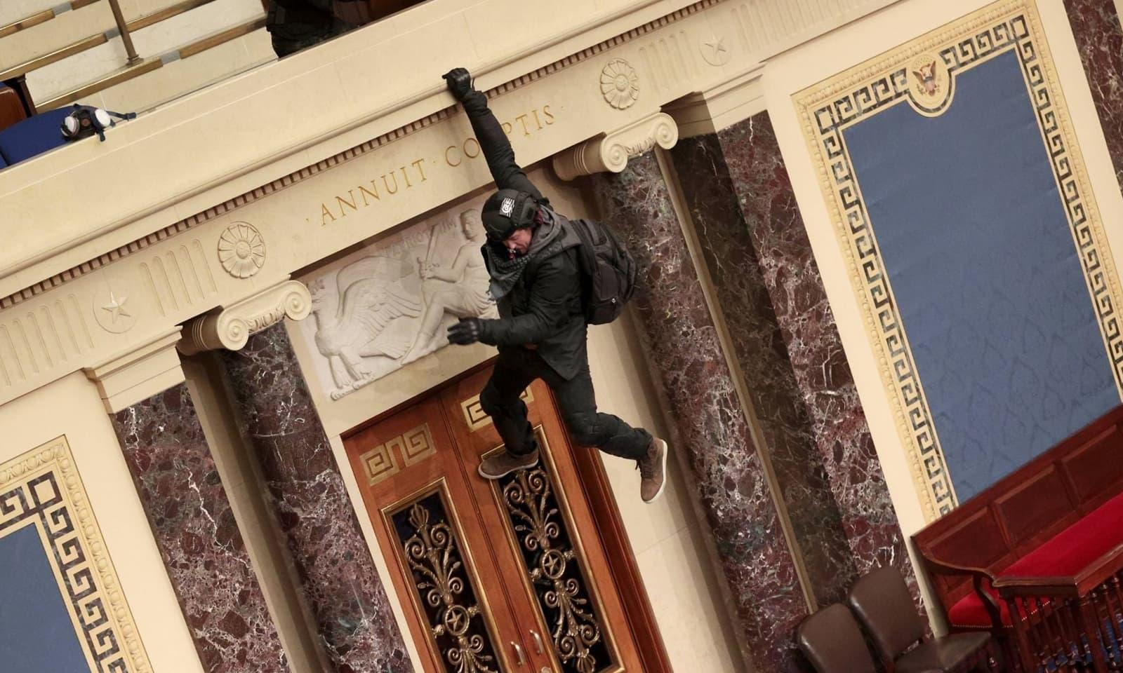 مظاہروں میں شریک ایک شخص سینیٹ چیمبر کی بالکونی پھلانگ رہا ہے— فوٹو:اے ایف پی