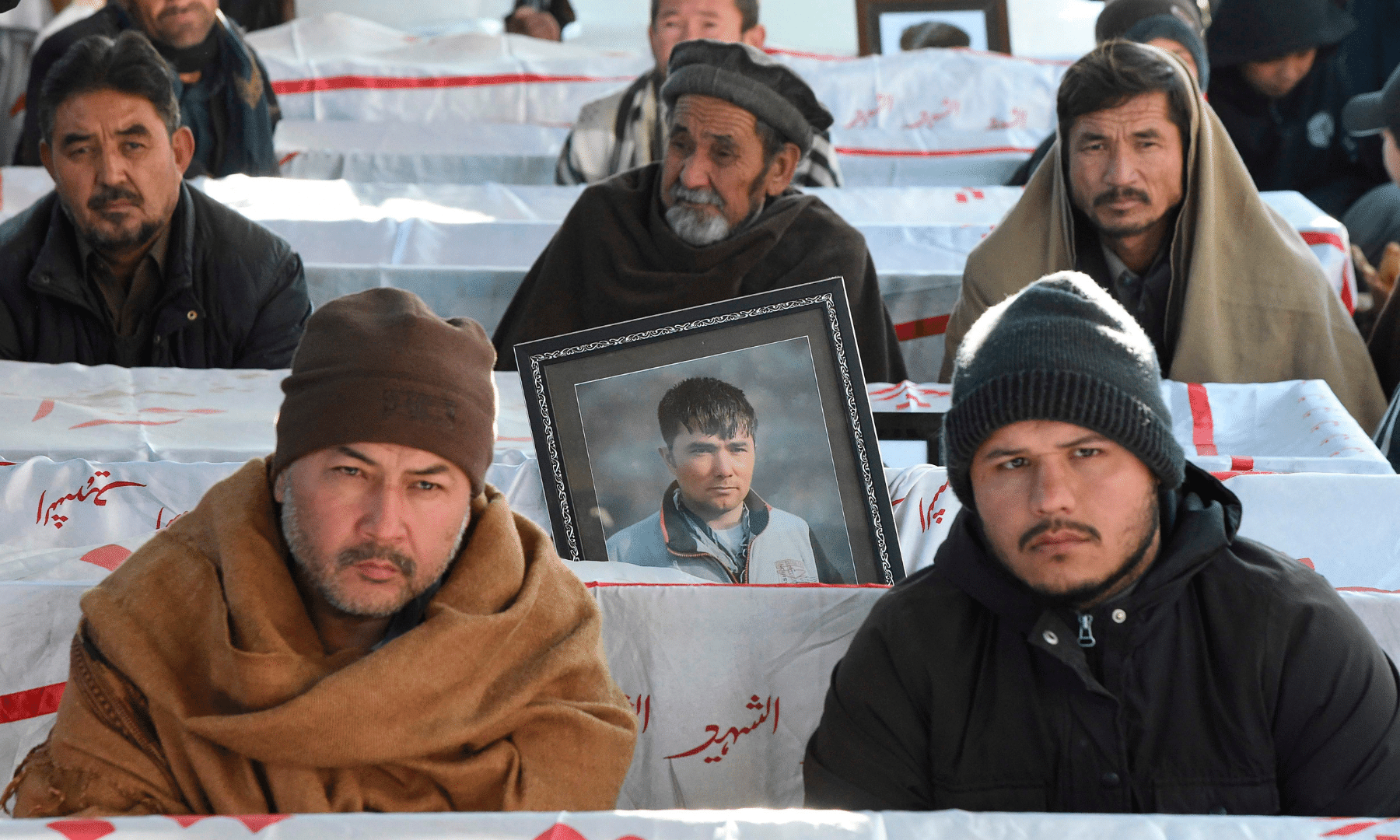 Mourners from the Shia Hazara community gather near the coffins of miners who were killed in an attack by gunmen in the mountainous Machh area, during a sit-in protest on the outskirts of Quetta on Jan 6. — AFP