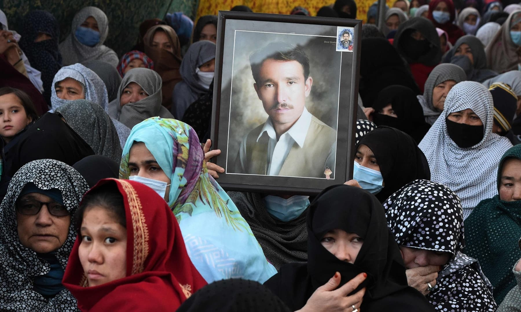 Mourners from the Shia Hazara community gather near coffins of the slain miners during a sit-in protest on the outskirts of Quetta on January 5. — AFP