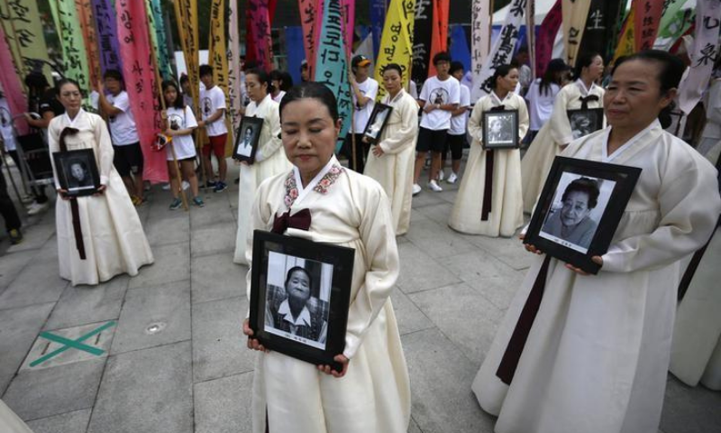 In this file photo, participants carry the portraits of Korean women who were made sex slaves by the Japanese military during World War II. — Reuters