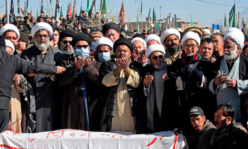 Mourners from the Shia Hazara community offer funeral prayers in front of coffins of the slain miners. — AFP