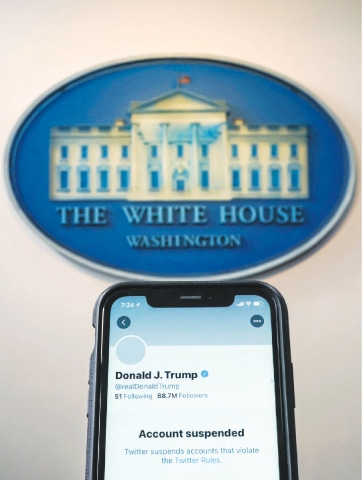 A photo illustration shows the suspended Twitter account of US President Donald Trump on a smartphone at the White House briefing room.—Reuters