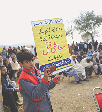 A child holds up a sign at a protest being staged by Daducha Dam affectees | Sibte Hassan Turi