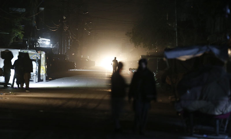 People are silhouetted on vehicle's headlights on a dark street during widespread power outages in Rawalpindi, Pakistan, on Sunday, Jan 10. Pakistan's national power grid experienced a major breakdown late night on Saturday, leaving millions of people in darkness. — AP