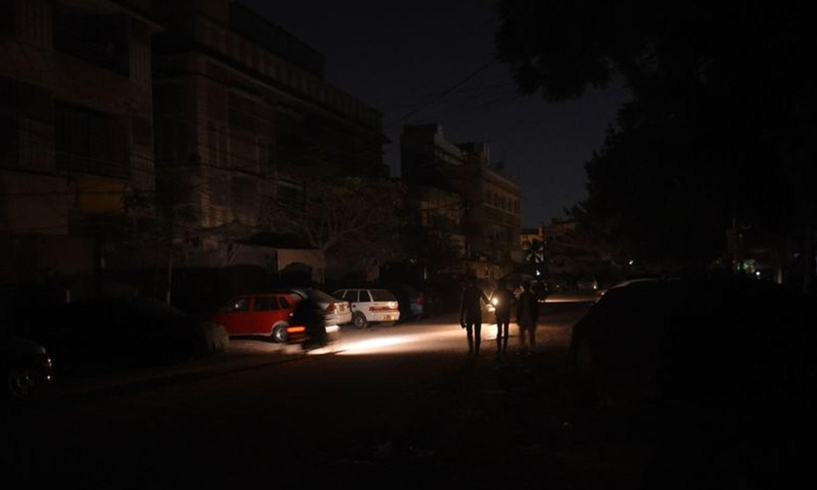 رات گئے ہونے والے بجلی کے بڑے بریک ڈاؤن کے بعد بتدریج بجلی کی بحالی کا کام جاری ہے— فوٹو: اے ایف پی