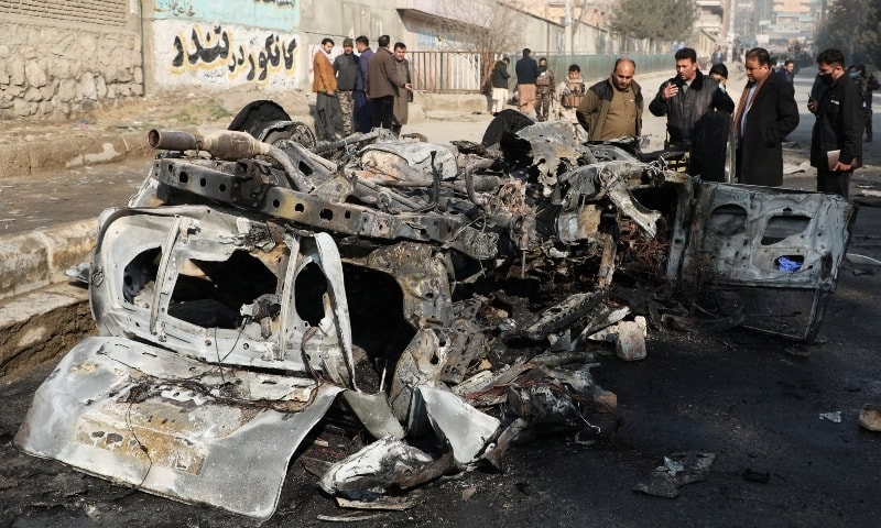 Afghan officials inspect the wreckage of a burnt car at the site of a bomb blast in Kabul, Afghanistan January 10. - Reuters