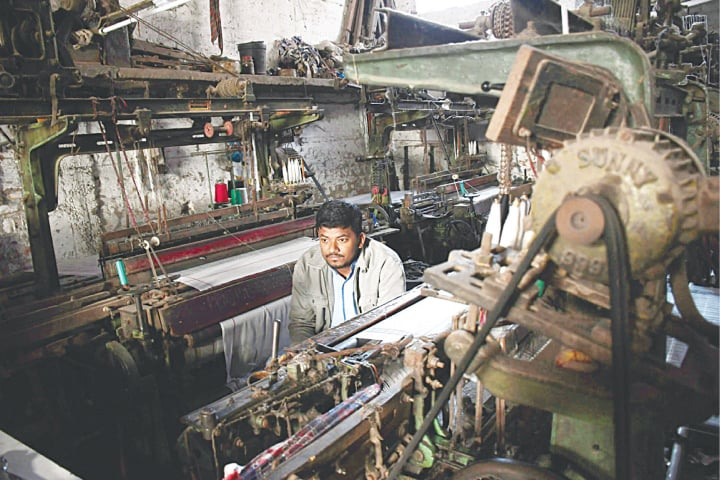 HYDERABAD: A worker sitting idle at a factory on Sunday before the electricity supply was restored.—Umair Ali